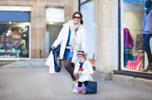 Happy young mother and her  toddler daughter enjoying shopping